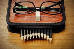 schwarze Bleistifte in einer Tasche und Gläser auf Braun Stockfotografie