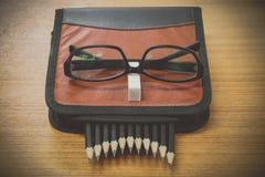 schwarze Bleistifte in einer Tasche und Gläser auf braunem Holz Stockfoto