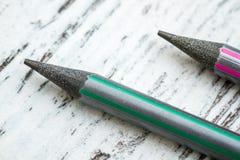 Schwarze Bleistifte mit buntem Körper auf weißem Hintergrund Stockfoto