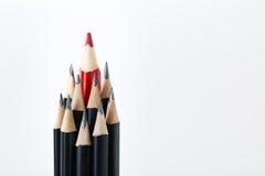 Schwarze Bleistifte mit einem roten in der Mitte Stockfotografie