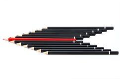 Schwarze Bleistifte mit einem roten in der Mitte Lizenzfreie Stockfotos