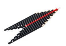 Schwarze Bleistifte mit einem roten in der Mitte Lizenzfreies Stockbild