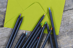 Schwarze Bleistifte und ein Umschlag Stockbilder