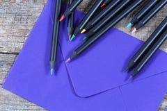 Schwarze Bleistifte und ein Umschlag Stockbild