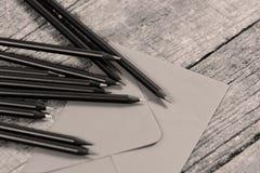 Schwarze Bleistifte und ein Umschlag Lizenzfreies Stockbild