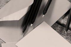 Schwarze Bleistifte und ein Umschlag Lizenzfreie Stockfotos
