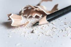 Schwarze Bleistiftschnitzel vom weißen Bleistift, lokalisiert auf weißem Hintergrund Lizenzfreies Stockbild