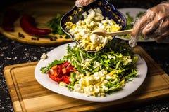 Schwarze Bohnen mit Gemüsepaprika auf einer weißen Platte und einem hölzernen Brett Überlagerungshand zerquetschte Eier stockfoto