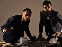Schwarze Buchhaltung Firma teilgenommen an illegalem Geschäft Männer bei Tisch mit Stapel von Geld- und Alkoholgetränken ungültig stockbilder