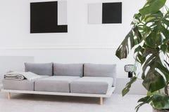 Schwarze der Zusammenfassung geometrische und graue Malereien auf wei?er Wand des modischen Wohnzimmerinnenraums lizenzfreie stockfotografie