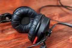 Schwarze DJ-Kopfhörer auf einem Holztisch lizenzfreies stockbild