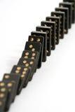 Schwarze Dominos, die in eine Zeile abfallen Stockbild