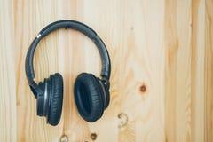 Schwarze drahtlose Kopfhörer hängen an einer hölzernen Wand Lizenzfreie Stockfotografie