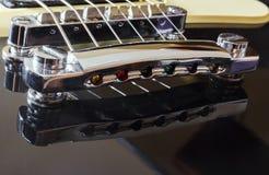 Schwarze E-Gitarre mit Stahlbrücke, Nahaufnahmemakro, schwarzer Körper Stockbilder