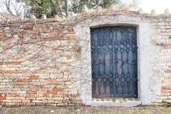 Schwarze Eisentür in einer Backsteinmauer, Burano, Italien Stockbild