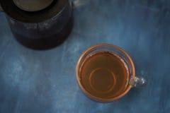 Schwarze Eisenteekanne und traditionelle keramische Tasse Tee mit Blütenrosablumen-Kirschniederlassung über grauem blauem Metallb lizenzfreies stockfoto