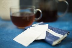 Schwarze Eisenteekanne und traditionelle keramische Tasse Tee mit Blütenrosablumen-Kirschniederlassung über grauem blauem Metallb lizenzfreies stockbild