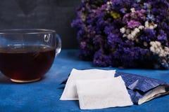 Schwarze Eisenteekanne und traditionelle keramische Tasse Tee mit Blütenrosablumen-Kirschniederlassung über grauem blauem Metallb stockfotos