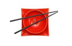Schwarze Ess-Stäbchen auf roter Schüssel und Quadrat überziehen ISO Stockbild