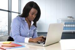 Schwarze Ethniefrau, die am Computerlaptopschreibtisch schreibt starke Funktion sitzt lizenzfreie stockfotografie