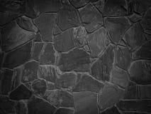 Schwarze Farbdekorative ungleiche gebrochene wirkliche Steinwand Stockfoto