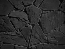 Schwarze Farbdekorative ungleiche gebrochene wirkliche Steinwand Stockfotografie