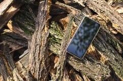 Schwarze Farbe des Handys sitzt im Freien auf einem Stapel der Barke von den Akazienbäumen lizenzfreie stockfotos