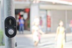Schwarze Farbfußgängerknopf mit den Unschärfehintergrundleuten, welche die Straße am sonnigen Tag kreuzen Stockbilder