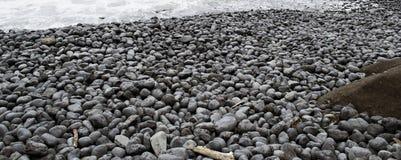 Schwarze Felsen auf einem Strand Lizenzfreies Stockfoto