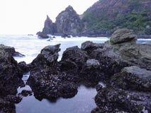 Schwarze Felsen an Dämmerung Watulumbungs-Strand Stockfotos