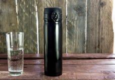 Schwarze Flasche mit Glas Wasser auf hölzerne Schreibtische lizenzfreie stockfotografie