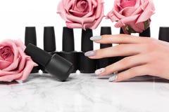 Schwarze Flaschen Nagellack auf einem Hintergrund von Blumen Manik?redesign stockbild