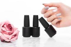 Schwarze Flaschen Nagellack auf einem Hintergrund von Blumen Manik?redesign stockbilder