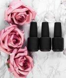 Schwarze Flaschen Nagellack auf einem Hintergrund von Blumen Manik?redesign stockfotos