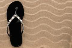 Schwarze Flipflops mit Bergkristallen auf dem gewellten Sand Stockfotografie