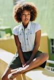 Schwarze Frau, Afrofrisur, tragende zufällige Kleidung in städtischem BAC lizenzfreies stockbild