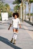 Schwarze Frau auf den Rollschuhen, die in der Strandpromenade mit Palmen rollerblading sind lizenzfreies stockbild