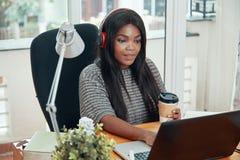 Schwarze Frau in den Kopfhörern, die an Laptop arbeiten lizenzfreie stockfotos