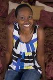 Schwarze Frau, die auf Bett sitzt Stockbilder