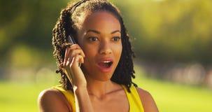 Schwarze Frau, die auf Smartphone in einem Park spricht Stockbild
