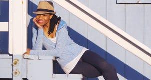 Schwarze Frau, die draußen auf Treppe sitzt stockfotografie