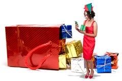 Schwarze Frau, die eine Weihnachtsverzierung öffnet Lizenzfreie Stockbilder