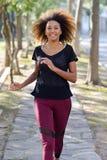 Schwarze Frau, die in einen städtischen Park läuft lizenzfreie stockbilder