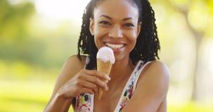 Schwarze Frau, die Eiscreme lächelt und isst Stockbild