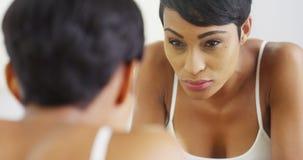 Schwarze Frau, die Gesicht mit Wasser spritzt und im Spiegel schaut Stockfoto