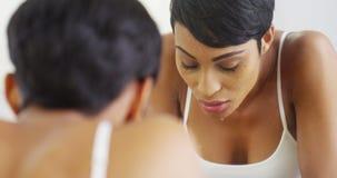 Schwarze Frau, die Gesicht mit Wasser spritzt und im Spiegel schaut Stockfotografie