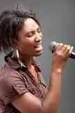 Schwarze Frau, die in Mikrofon singt Stockfoto