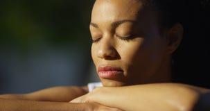 Schwarze Frau, die mit den Augen draußen geschlossen sitzt stockfotos
