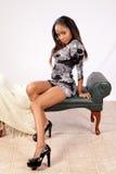 Schwarze Frau, die mit der Kamera sitzt und flirtet Lizenzfreies Stockfoto