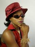 Schwarze Frau, die rote Huthand auf Kinn trägt Stockfotografie